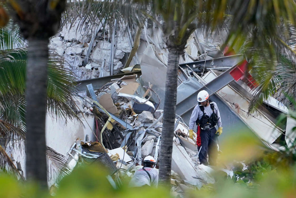 Slide 24 of 58: Rescue workers walk among the rubble where part of a 12-story beachfront condo building collapsed, Thursday, June 24, 2021, in Surfside, Fla.