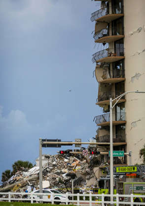 Slide 7 of 34: Police cars are parked in front of debris from a partially collapsed building in Surfside north of Miami Beach, on June 24, 2021. - A high-rise oceanfront apartment block near Miami Beach partially collapsed early Thursday, killing at least one person and leaving 99 unaccounted for, with fears the toll may rise much higher as rescuers combed through the rubble.