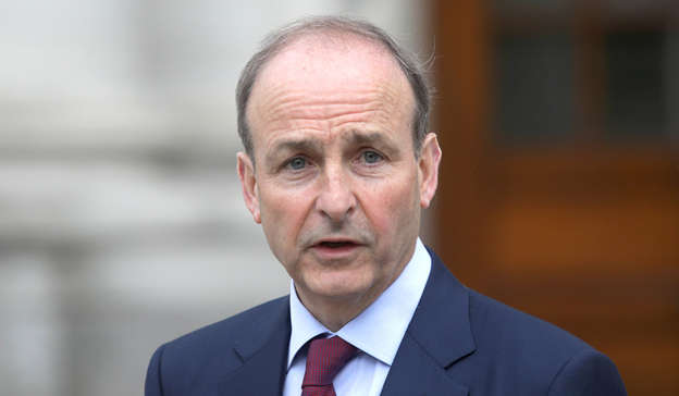 Micheal Martin wearing a suit and tie: On Tuesday afternoon, Taoiseach Micheál Martin confirmed that the resumption of indoor dining will be postponed until July 19 at the earliest to facilitate the development of a vaccination verification system. Pic: Gareth Chaney / Collins Photos Dublin