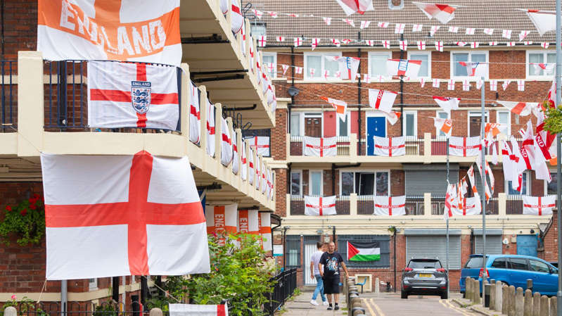 a group of people standing in front of a building: The Kirby Estate, in Bermondsey, south London, is decorated with England flags