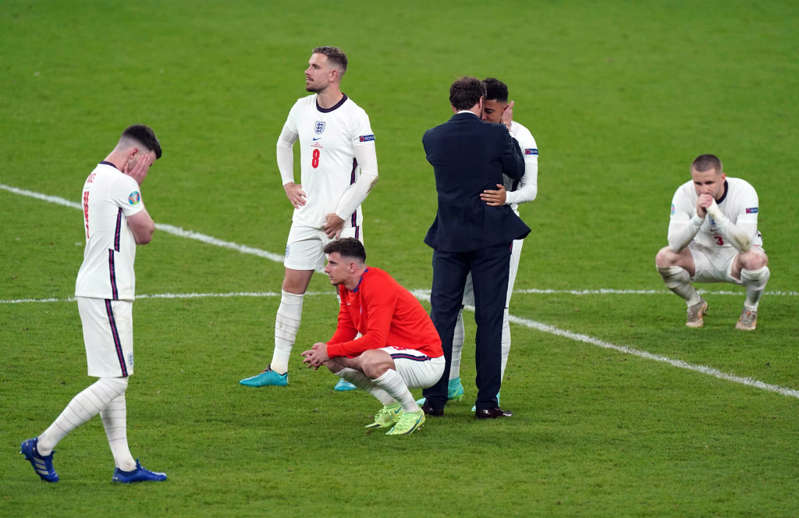 a group of people playing football on a field: England manager Gareth Southgate consoles Jadon Sancho after his penalty miss following the UEFA Euro 2020 Final at Wembley Stadium, London. Picture date: Sunday July 11, 2021. (Photo by Mike Egerton/PA Images via Getty Images)