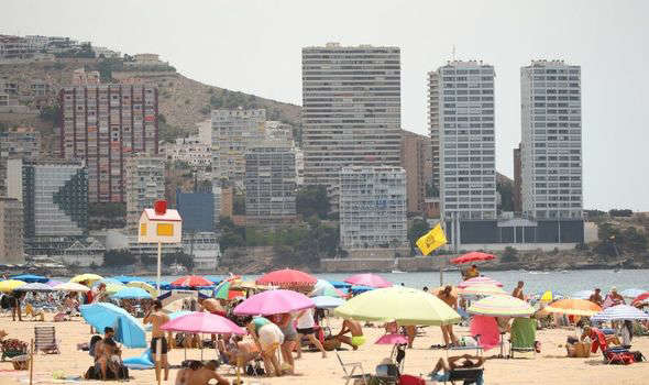 a group of people sitting at a crowded beach: Holidays