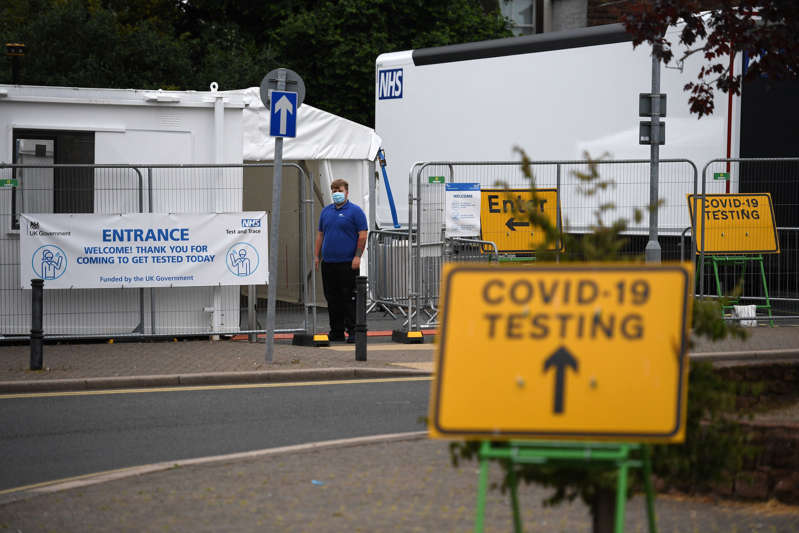 Workers wait to receive members of the public queue at a temporary Covid-19 testing centre set up a car park in Penrith in Cumbria, north west England on June 21, 2021, following an outbreak of a coronavirus variant of concern. (Photo by Oli SCARFF / AFP) (Photo by OLI SCARFF/AFP via Getty Images)