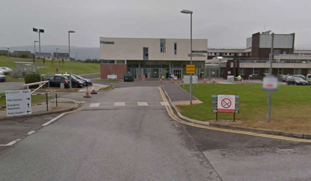 a sign on the side of a road: The exhumation started at first light and the remains were brought to Kerry University Hospital in Tralee. Pic: Google Street View