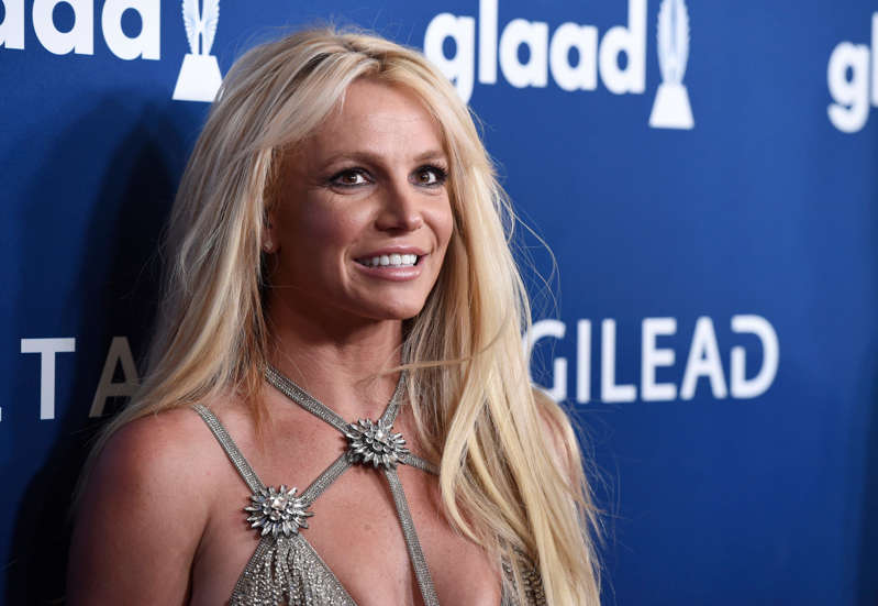 a woman smiling for the camera: In this April 12, 2018 file photo, Britney Spears arrives at the 29th annual GLAAD Media Awards at the Beverly Hilton Hotel in Beverly Hills, Calif.  Spears is putting her planned Las Vegas residency on hold to focus on her father's recovery from a recent life-threatening illness. The pop superstar announced Friday, Jan. 4, 2019 she is going on an indefinite work hiatus.