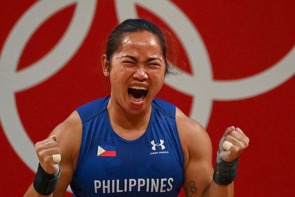 Hidilyn Diaz holding a sign posing for the camera: Hidilyn Diaz of the Philippines reacts after placing first in the women's 55 kg weightlifting competition during the Tokyo Olympic Games. (Vincenzo Pinto/AFP via Getty Images)
