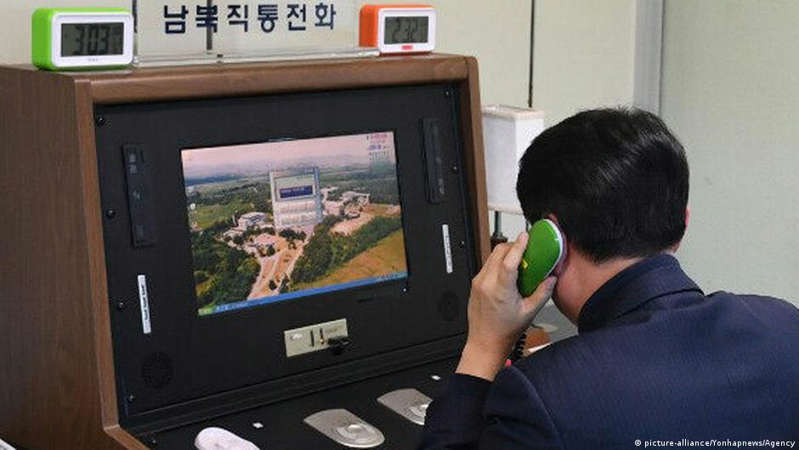 a man talking on a cell phone in front of a television: Communication between North and South Korea takes place at liaison offices