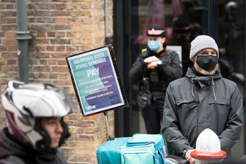 a man and a woman standing in front of a building: In July, the Court of Appeal ruled that Deliveroo riders are not workers and therefore not entitled to collective bargaining rights (Stefan Rousseau/AP) (PA Wire)