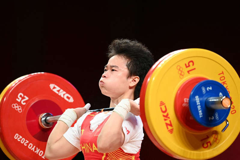 a man holding a frisbee: China's Hou Zhihui competes in the women's 49kg weightlifting competition - AFP
