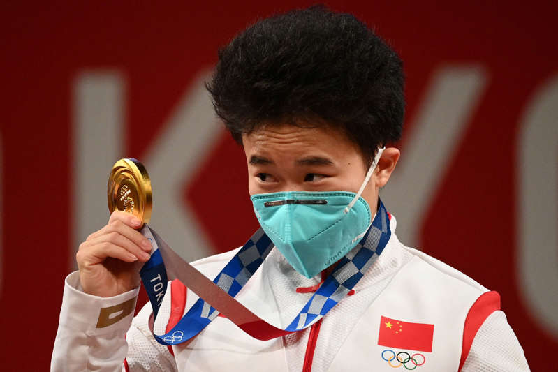 a man wearing a suit and tie talking on a cell phone: China's Hou Zhihui stands on the podium after winning gold (AFP)