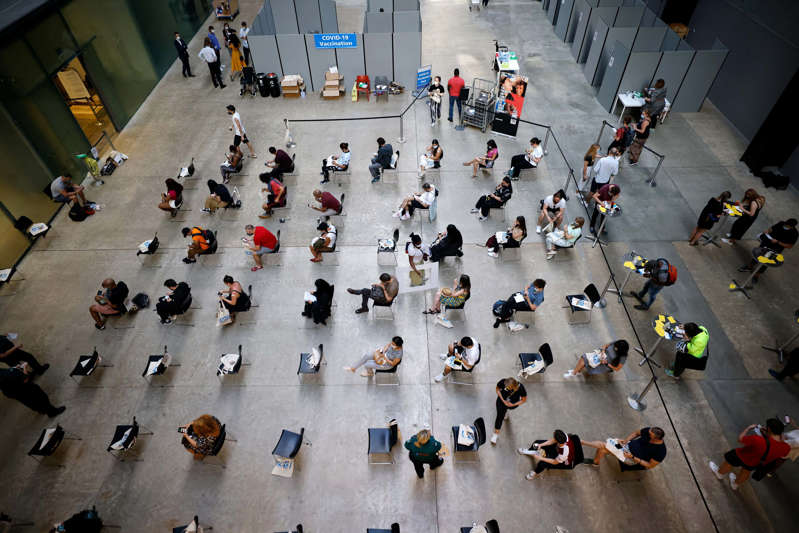 Members of the public wait on socially distanced chairs to receive the Pfizer-BioNTech Covid-19 vaccine in the Turbine Hall