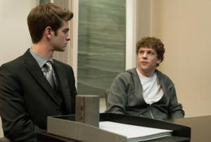 Jesse Eisenberg wearing a suit and tie: Andrew Garfield and Jesse Eisenberg in *The Social Network.*