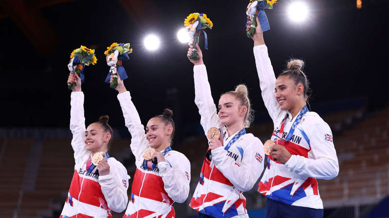 a group of people standing on a stage: Team GB's (L-R) Jennifer Gadirova, Jessica Gadirova, Alice Kinsella and Amelie Morgan with their bronze medals