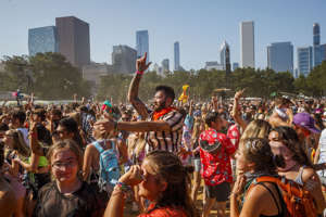 a group of people standing in front of a crowd: Music fans dance at the Perry's stage during the last day of the 2019 Lollapalooza Music Festival in Grant Park in 2019. Last year's festival was canceled because of COVID-19.
