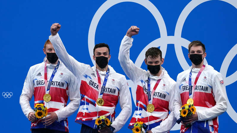 a man holding a hot air balloon in the sky: Team GB have won four medals in swimming event, three of which were golds