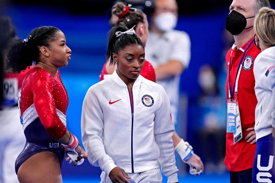 a group of football players on a field: Simone Biles