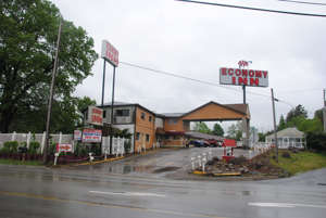 a sign on the side of a road: The Economy Inn at 1138 N. Center Avenue in Somerset is the home of the former Coleman Motel, where the Shuglie family had been staying when Janet and Marisa disappeared.