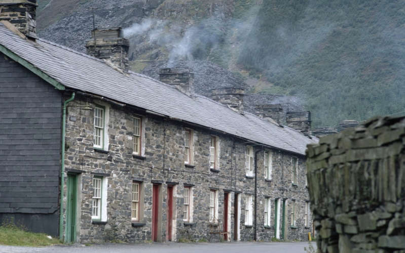 an old brick building with a mountain in the background: Stone houses at the slate quarry of Dinorwig - Getty
