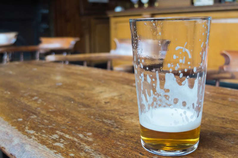 a glass cup on a wooden table: drinking beer pint