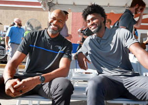 a group of people sitting on a bench: New Orlando Magic head coach Jamahl Mosley and Magic forward Jonathan Isaac, right, during a topping-off ceremony for the construction of the AdventHealth Training Center at Amway Center on July 21, 2021.