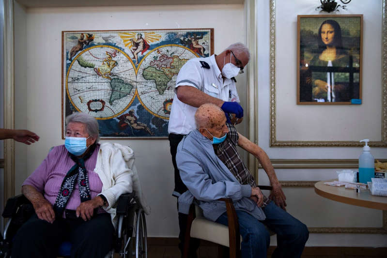 a group of people sitting in a room: A man receives his second Pfizer vaccine at a nursing home in Ramat Gan. All over 60s will soon be offered a third vaccine. - AP