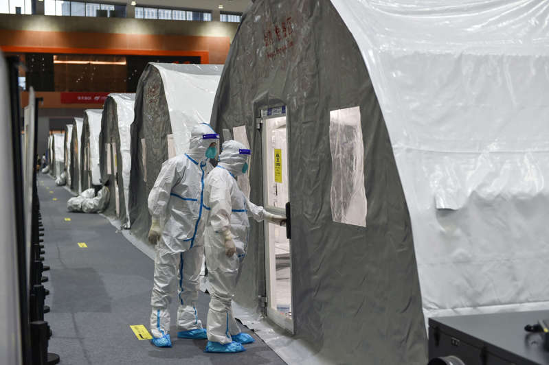"""a person standing in front of a store: Staff checking a unit at a temporary """"Fire Eye"""" laboratory used for coronavirus testing in Nanjing (AFP via Getty Images)"""
