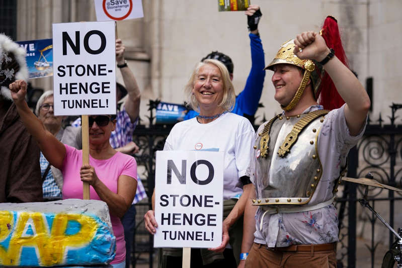 a group of people holding a sign: Stonehenge road project