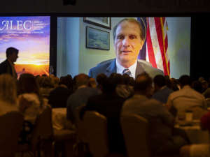Chris Stewart et al. sitting in front of a television: Utah Congressman Chris Stewart speaks at the American Legislative Exchange Council breakfast session via Zoom as the group gathers at the Grand America Hotel in Salt Lake City on Friday.