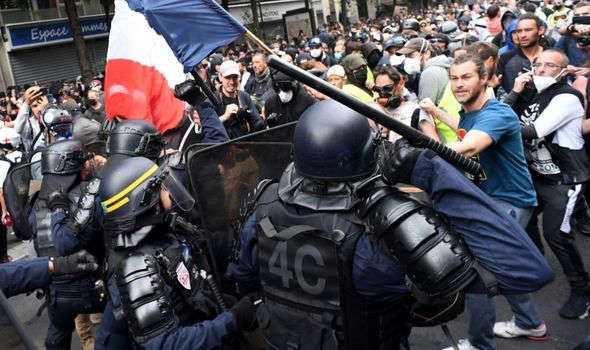 a group of people riding on the back of a motorcycle: France protests