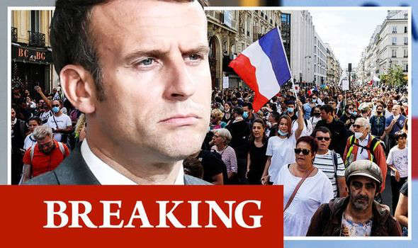 Emmanuel Macron holding a sign in front of a crowd: France protests