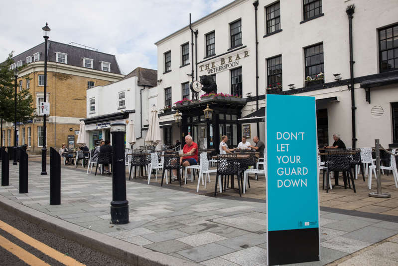 A Covid-19 public health information sign is pictured in front of local residents enjoying refreshments outside a JD Wetherspoon public house on 27th July 2021 in Maidenhead, United Kingdom. (photo by Mark Kerrison/In Pictures via Getty Images)