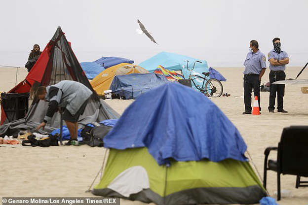 a group of people in a tent: The law specifies certain times and locations where it will be 'unlawful for a person to sit, lie, or sleep, or to store, use, maintain, or place personal property in the public right-of-way,' the ordinance reads