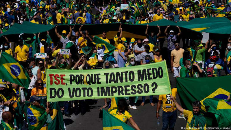 a group of people standing in front of a crowd: A pro-Bolsonaro protester holds a banner calling for adding printouts to the electronic voting system