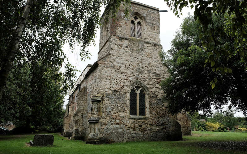 a large brick building with a clock tower in front of a house: St Mary Magdalene Caldecote in Hertfordshire