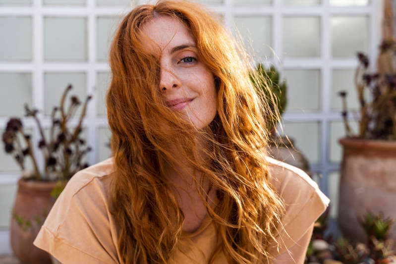 a woman smiling for the camera: Portrait of smiling redheaded young woman on terrace