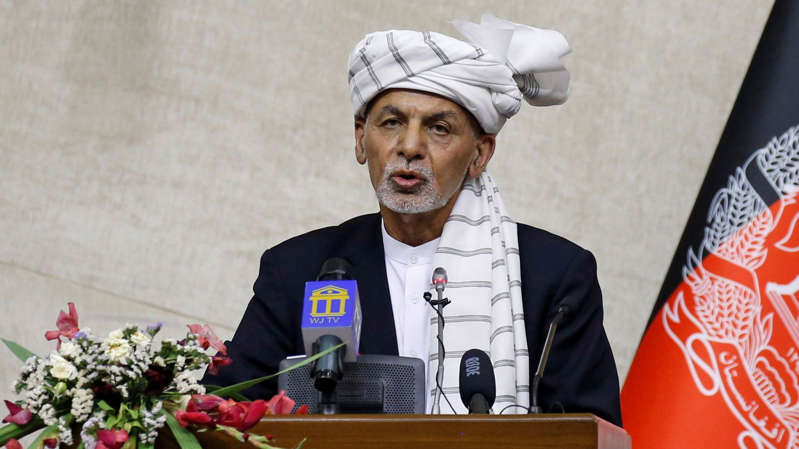 Ashraf Ghani with a vase of flowers on a table: Afghan President Ashraf Ghani is pictured speaking inside parliament in Kabul