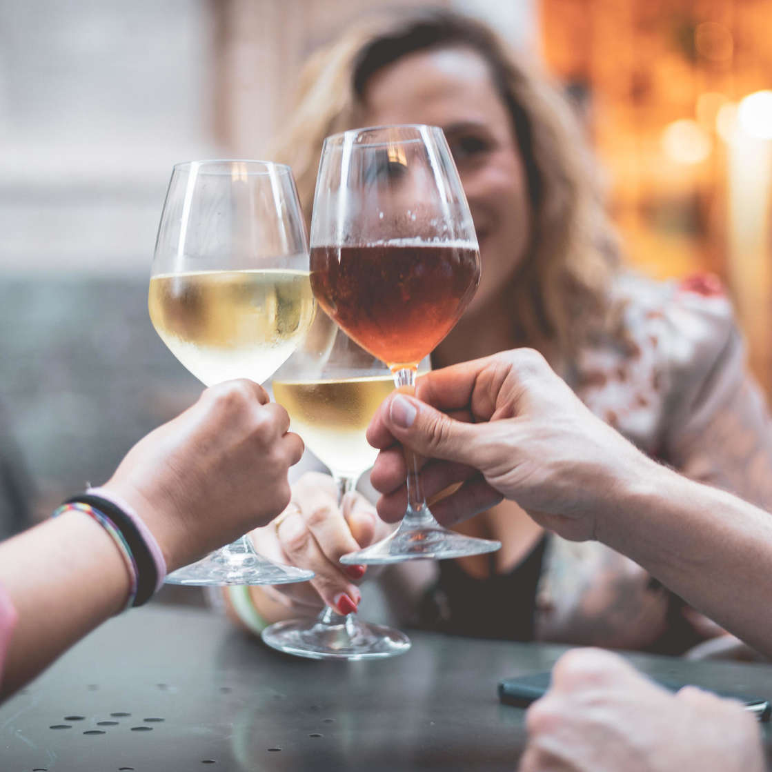 a hand holding a glass of wine: Friends Toasting Wineglasses In Restaurant