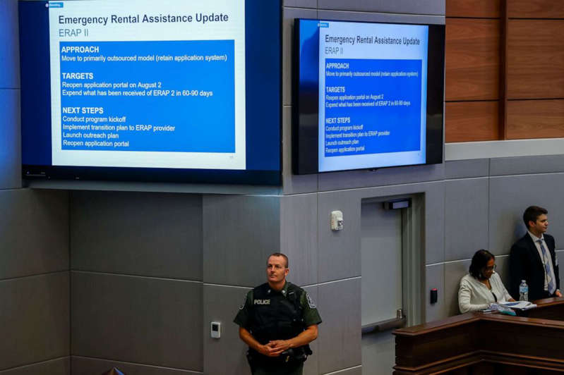 a group of people standing in front of a computer: A Fulton County Police officer stands below information to assist renters overdue or financially stressed on their housing rental payments in Atlanta, Aug. 2, 2021.