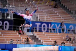 Simone Biles jumping into the air to catch a frisbee: Simone Biles competes on the balance beam.