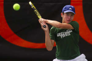 a person hitting a ball with a racket: Ann Arbor Greenhills' Mert Oral swings to return a ball during the 2019 MHSAA Division 3 Boys Tennis Finals at Kalamazoo College in Kalamazoo, Michigan on Saturday, October 19, 2019.