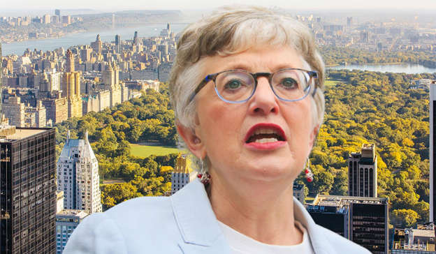 Katherine Zappone wearing glasses and standing in front of a large city landscape