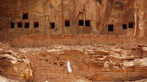 a cliff next to a brick wall: The 2,600-year-old rock-cut tombs of Al-Khuraiba, in Saudi Arabia.