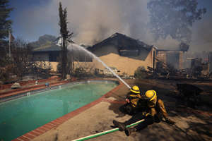 a lot of smoke around it: Firefighters take a defensive stand against a home burning in Redwood Valley, Calif., ignited by an 80 acre wind whipped brush fire fed by tinder dry conditions on July 7.