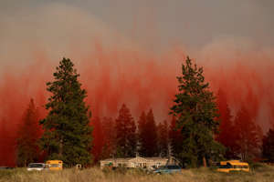 a sunset over a forest: Fire retardant dropped from an airplane falls to the ground near the Chuweah Creek Fire as wildfires devastate Nespelem, Wash. on July 14.   David Ryder—Reuters