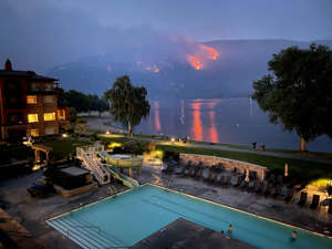 a body of water with a city in the background: View of a beach resort as a wildfire burns on a hillside in Osoyoos, British Columbia, Canada, on July 20.   Sara Mahony—Reuters