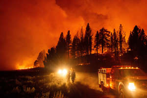 bright city lights at night: Firefighters battle the Sugar Fire, part of the Beckwourth Complex Fire, burning in Plumas National Forest, Calif., on July 8.   Noah Berger—AP