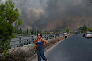 a man riding a skateboard up the side of a road: Forest fire rages in Varybobi, north of Athens, Greece on Aug. 3. Residential areas in Athens northern suburbs were evacuated as wildfires reached the outskirts of the city.   Gerasimos Koilakos—NurPhoto/Getty Images