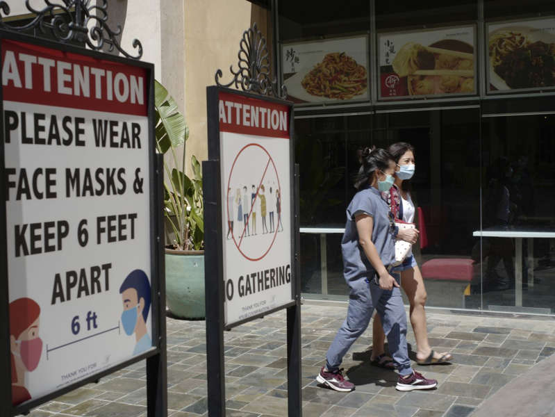 a person holding a sign: Customers wear face masks in an outdoor mall with closed businesses amid the COVID-19 pandemic in Los Angeles on June 11, 2021. Coronavirus cases have jumped 500% in Los Angeles County over the past month.