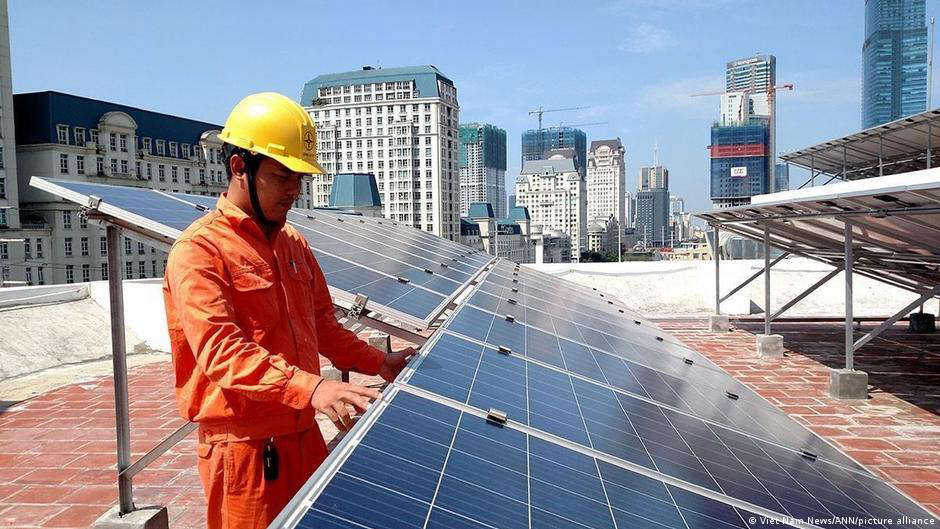 a person standing in front of a building: Vietnam is experiencing a solar energy boom