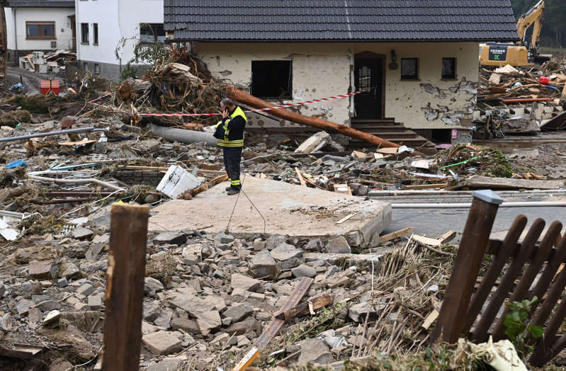 """A firefighter speaks on the phone as he stands amid debris of destroyed houses after the floods caused major damage in Schuld near Bad Neuenahr-Ahrweiler, western Germany, on July 17, 2021. - Devastating floods in Germany and other parts of western Europe have been described as a """"catastrophe"""", a """"war zone"""" and """"unprecedented"""", with more than 150 people dead and the toll still climbing on July 17, 2021 (Photo by CHRISTOF STACHE / AFP) (Photo by CHRISTOF STACHE/AFP via Getty Images)"""